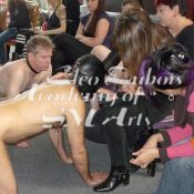 A line of volunteer bottoms lines up in front of participants for hands on development of Dominance techniques at an Academy of SM Arts Erotic Dominance Intensive Course for Professionals